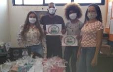 Pra cego ver: Participantes do projeto entregando as máscaras para comunidade. Foto posada,com os quatro segurando as máscaras de tecido entregues. Fim da descrição.
