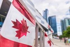 Bandeira do Canadá, pendurada no mastro, em primeiro plano. E ao fundo, prédios grandes e espelhados.