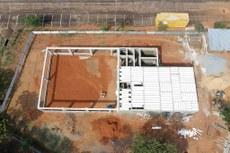 Pra cego ver: Imagem aérea da obra em construção na unidade de Palmas. Trata-se de um canteiro de obra do refeitório. Compõem a foto elementos como: terra, árvores em volta, divisão de espaços já erguidos, espaços abertos e cobertos. Fim da descrição.