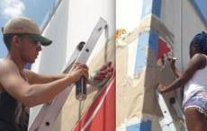 Pra cego ver: estudantes durante projeto de extensão, que leva arte urbana e grafite a Rio da Conceição. Os dois estudantes estão em escadas, com tintas e pintando as paredes sem cor ainda. Fim da descrição.